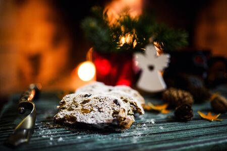 Christmas stollen on the background of a burning fireplace. Traditional German, European festive dessert. Stock Photo