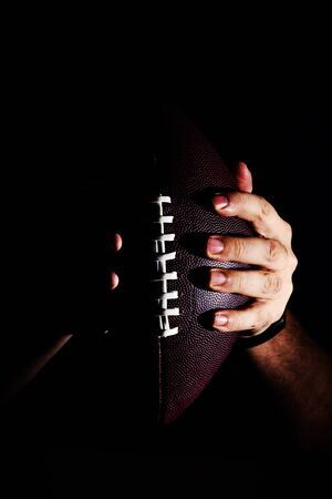 hand holding American football ball isolated on black background