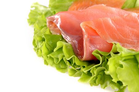 Sliced salmon fish on green salad isolated on white background