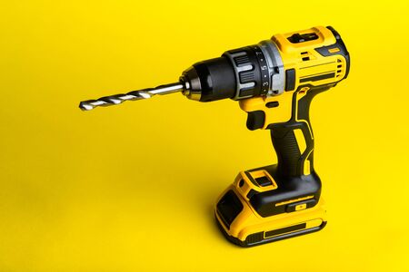 cordless drill and a drill on a yellow background