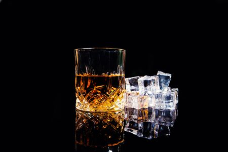 whiskey with ice cubes on black background