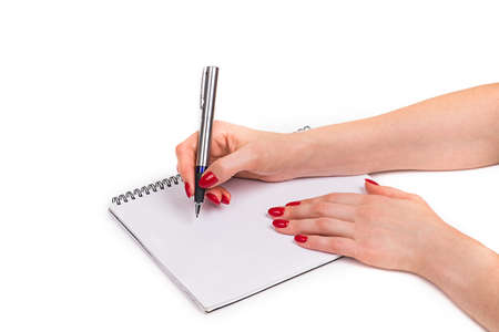 Nails Design. Hands With Bright Red Christmas Manicure On White Background. Close Up Of Female Hands. Art Nail. woman writes with a pen in a notebook