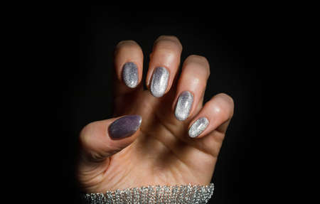 Nails Design. Hands With Bright Silver Christmas Manicure On Black Background. Close Up Of Female Hands. Art Nail.