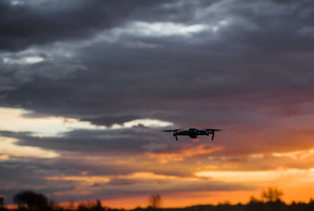 drone quadcopter with digital camera at beautiful sunrise sky.