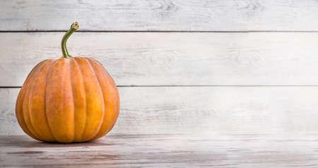 Pumpkin on a white wooden background.