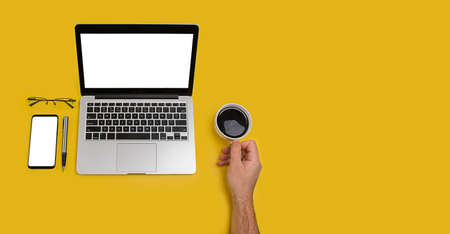 Laptop, smartphone, notebook and glasses on yellow background. Working from home concept.