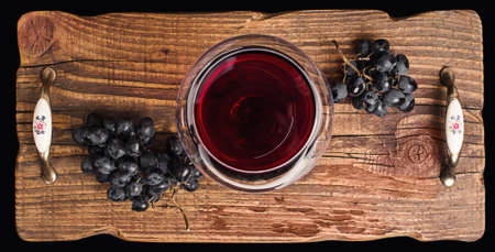 Red wine in a glass and ripe grapes on rustic textured wooden tray. 版權商用圖片