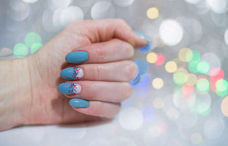 Nails Design. Hands With Snowman on Christmas Background and Defocused Lights. Manicure On Black Background. Close Up Of Female Hands. Art Nail.