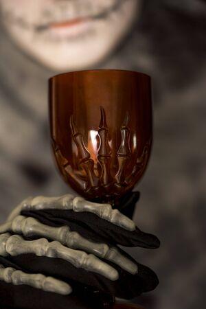 goblet: Skeleton holding a red goblet