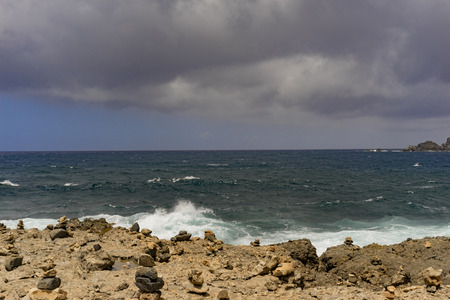 stormy sea: Stormy sea at stony shore with dark clouds in the back