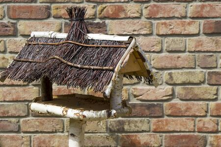 brickwalls: Empty handmade bird house in front of brick wall