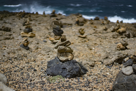 stormy sea: Stone piles in front of a stormy sea on a stony beach Stock Photo