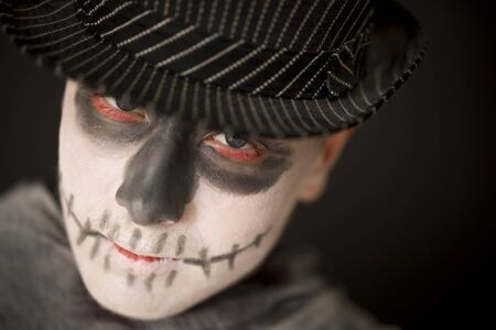 ghoulish: Spooky young man in Halloween costume wearing skull makeup and a dark hat and cloak looking up at the camera with red rimmed eyes, close up of his face