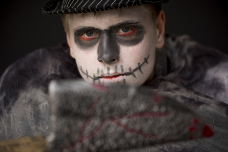 ghoulish: Young man in ghoulish Halloween skull makeup wrapped in dark clothing and hat brandishing a bloodied knife at the camera, focus to his face Stock Photo