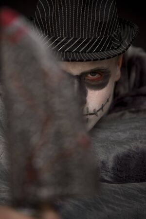 Sinister Halloween trick-or-treater wearing skull makeup and a dark hat hiding behind a bloodied cleaver which he is brandishing at the camera, focus to his face