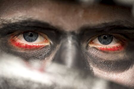 ghoulish: Eyes of a man wearing skull makeup with bloodshot rims and deep shadowed eye sockets looking at the camera over the blade of a knife, Halloween horror concept Stock Photo