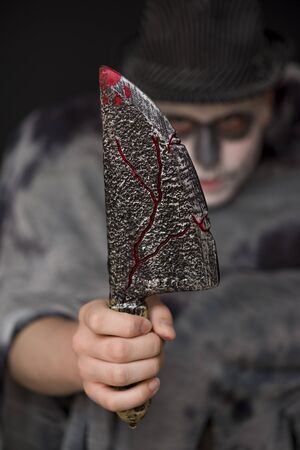 brandishing: Halloween horror with a young man in skull makeup and costume brandishing a blood stained knife at the camera, focus to the blade Stock Photo