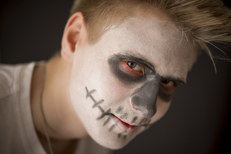 ghoulish: Young man in Halloween or skull makeup with dark red rimmed eye sockets as he prepares to celebrate the Day of the Dead or Halloween
