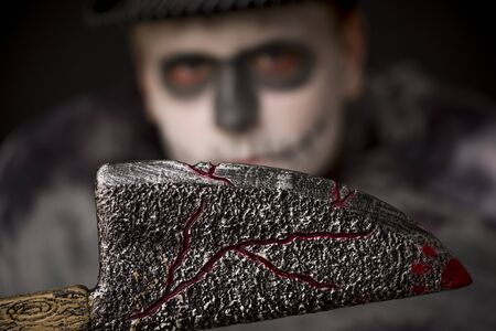 Sinister wooden bloodied Halloween meat cleaver held in the darkness by a man in ghoulish skull makeup, focus to the knife