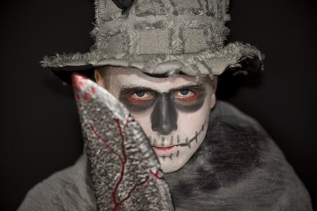 ghoulish: Young man standing in darkness wearing skull makeup, an old battered hat and Halloween costume holding up a bloody meat cleaver, focus to the face