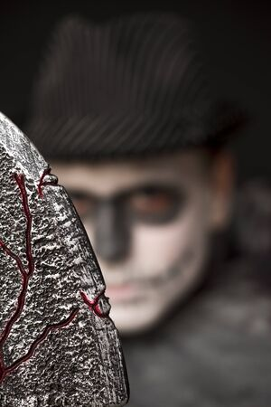Sinister Halloween costume with a man wearing skull makeup and a dark hat and robe brandishing an old bloodied textured knife at the camera, focus to the blade