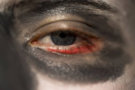 eye socket: Close up of the eye of a person wearing skull makeup for Halloween wirh a darkened eye socket and red rim around the eye