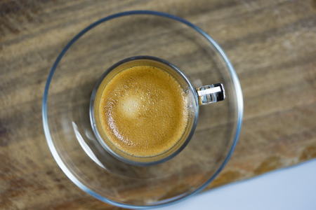 addictive drinking: Cup of strong frothy espresso coffee in a glass mug viewed from overhead on a rustic wooden table Stock Photo