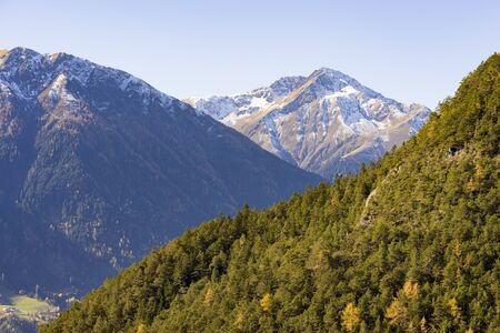 intermittent: Alpine landscape in Tyrol, Austria with high mountain peaks and steep forested slopes scattered snow with intermittent trees showing colorful autumn foliage Stock Photo