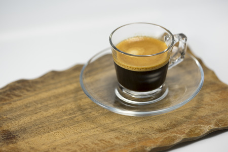 addictive drinking: Cup of frothy espresso coffee energizing strong in a glass cup and saucer served on a rustic wooden tray
