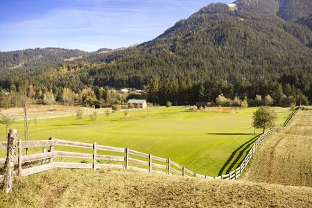 fenced in: Scenic Landscape View of Green Farm with Fenced Field Nestled Amongst Rolling Foothills in Mountainous Forested Alpine Region, Tyrol, Austria on Sunny Day Stock Photo