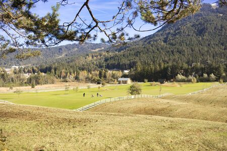 fenced in: Scenic Landscape View of Green Farm with Fenced Field Nestled Amongst Rolling Foothills in Mountainous Forested Alpine Region, Tirol, Austria on Sunny Day Stock Photo