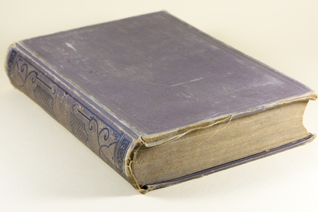 discolored: Old vintage hardcover book with a tattered cover and binding and discolored pages lying on a neutral background viewed corner on
