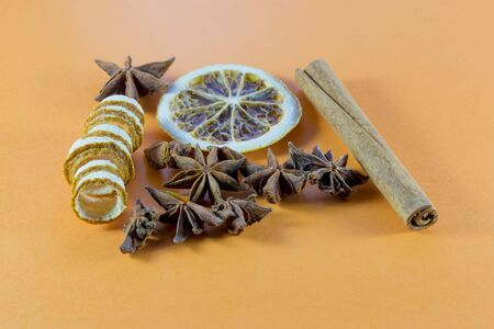 stick of cinnamon: Winter spices for a festive occasion with orange, star anise, stick cinnamon and coiled citrus peel on an orange background with copy space for your Christmas or seasonal greeting