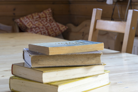 discolored: Pile of old hardcover books on a rustic table alongside a wooden chair inside a house with copy space above