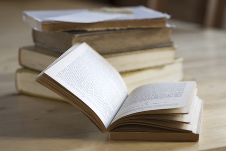 discolored: Old vintage book opened to a double spread in front of a stack of worn hardcover books on a rustic wooden table