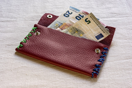 maroon leather: 5, 10 and 20 Euro banknotes in an open maroon leather purse