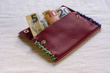 5 to 10: 5, 10 and 20 Euro banknotes in an open purse or wallet