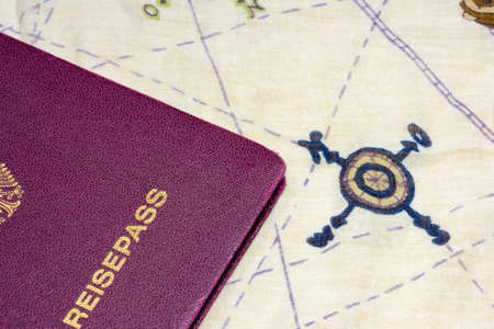 viewable: Red colored German passport partially viewable over cloth map with the four cardinal directions