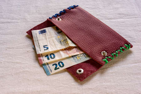denominations: Euro banknotes in different denominations, protruding from an open purse on a table, Stock Photo