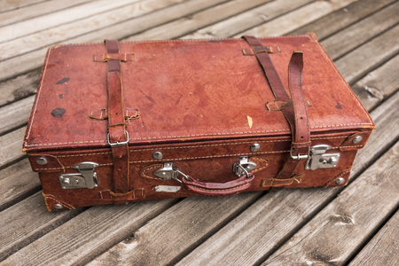 holiday budget: Old worn vintage brown leather suitcase with straps on a wooden deck in a travel and vacation concept Stock Photo