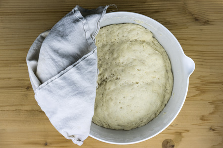 batters: Top down view of bread batter rising in bowl. Cloth rag on top to cover it for enhancing the speed of yeast activation
