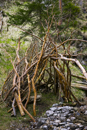hideout: Rustic Lean-To Shelter Constructed from Tree Branches Beside Small Rocky Creek in Forest Setting Stock Photo