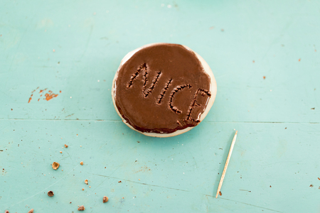 punched out: Chocolate cookie with the word Nice on it punched out with a wooden toothpick in the topping over a turquoise background with crumbs and copy space