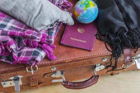 pyjama: High Angle Close Up of Travel Vacation Concept Image - Brown Leather Suitcase with Plaid Pyjama Pants, Black Fringed Pashmina Wrap, Miniature Globe and German Passport Stock Photo