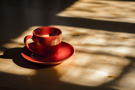 ample: Profile Still Life of Red Cup of Coffee with Saucer on Wooden Kitchen Table with Bright Sunlight Streaming Through Window with Shadows and Ample Copy Space