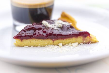Slice of fresh berry pie or flan served on a plate with a glass of strong black espresso coffee in a close up low angle view