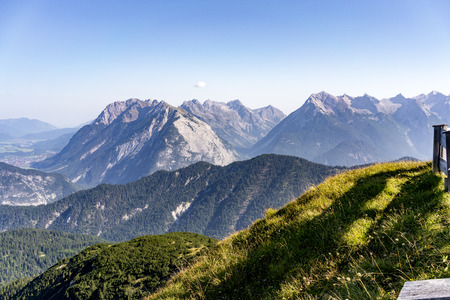 Picturesque alpine landscape in summer with rugged mountain peaks and steep valleys taken from a high altitude lookout point Stock Photo