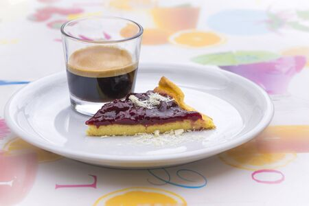 Slice of fresh berry pie and strong black frothy espresso coffee served in a glass on a generic white plate on a colorful tablecloth
