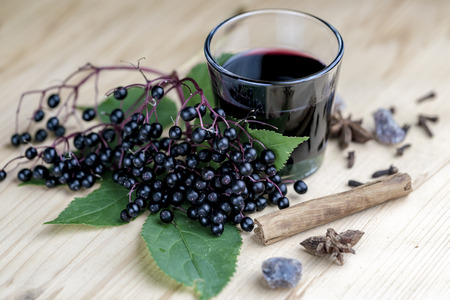 Glass of fresh elderberry syrup with cinnamon stick, brown sugar, star anise and elderberries on a wooden kitchen counter