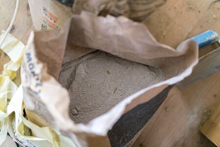 opened bag: Opened bag of dry cement viewed from above on a building site in a construction or renovation concept